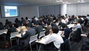 大阪会場。スクリーンに東京の講演の映像とスライドが映っている。